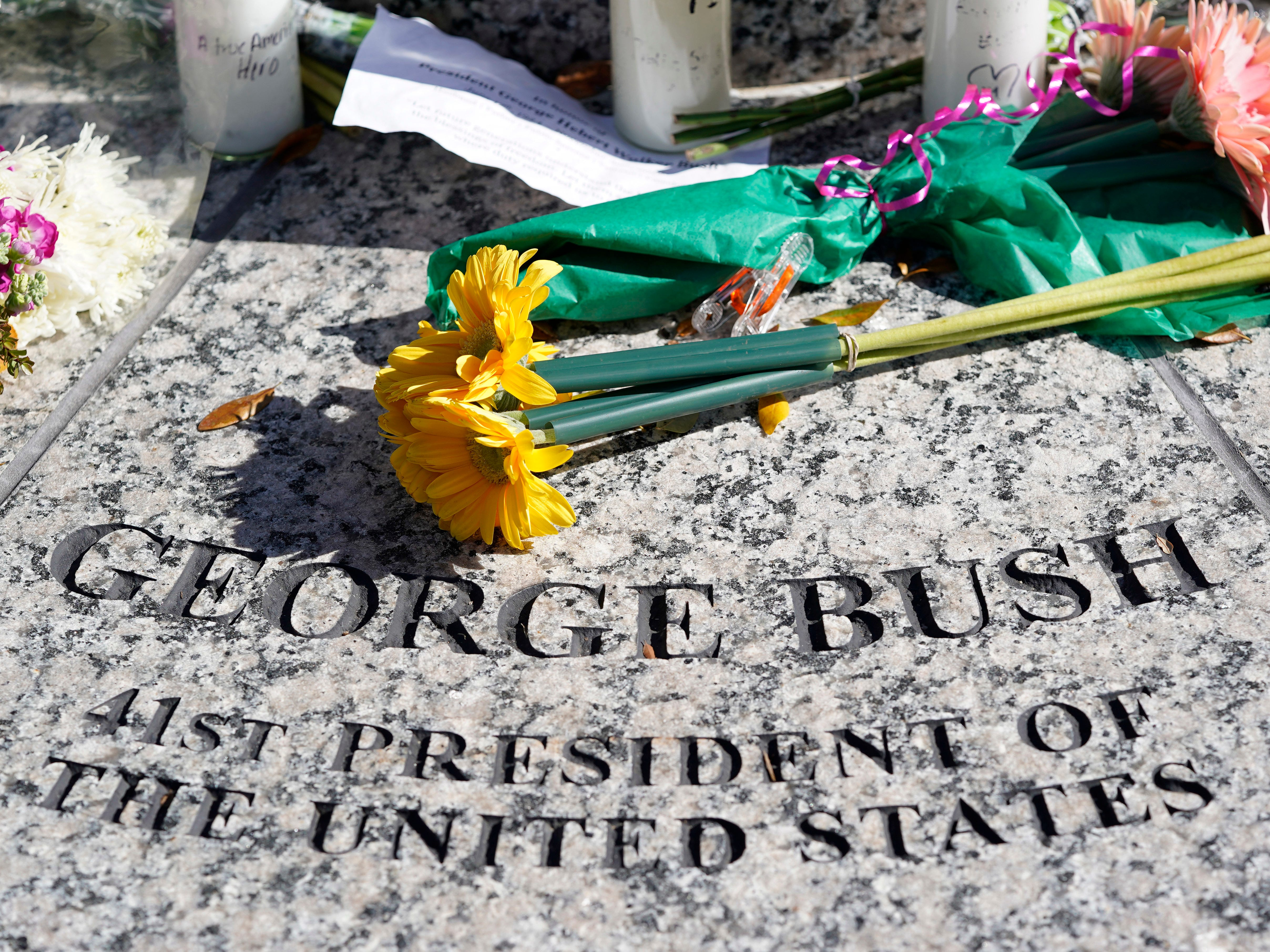 Flowers are placed at the foot of a statue of George H.W. Bush outside the George H.W. Bush Presidential Library and Museum Saturday, Dec. 1, 2018, in College Station.