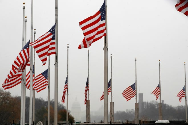 With a misty U.S. Capitol in the distance, the American flags surrounding the Washington Monument fly at half-staff, Saturday, Dec. 1, 2018, in Washington, after President Donald Trump directed that American flags be flown at half-staff for 30 days to honor the memory of former President George H.W. Bush.