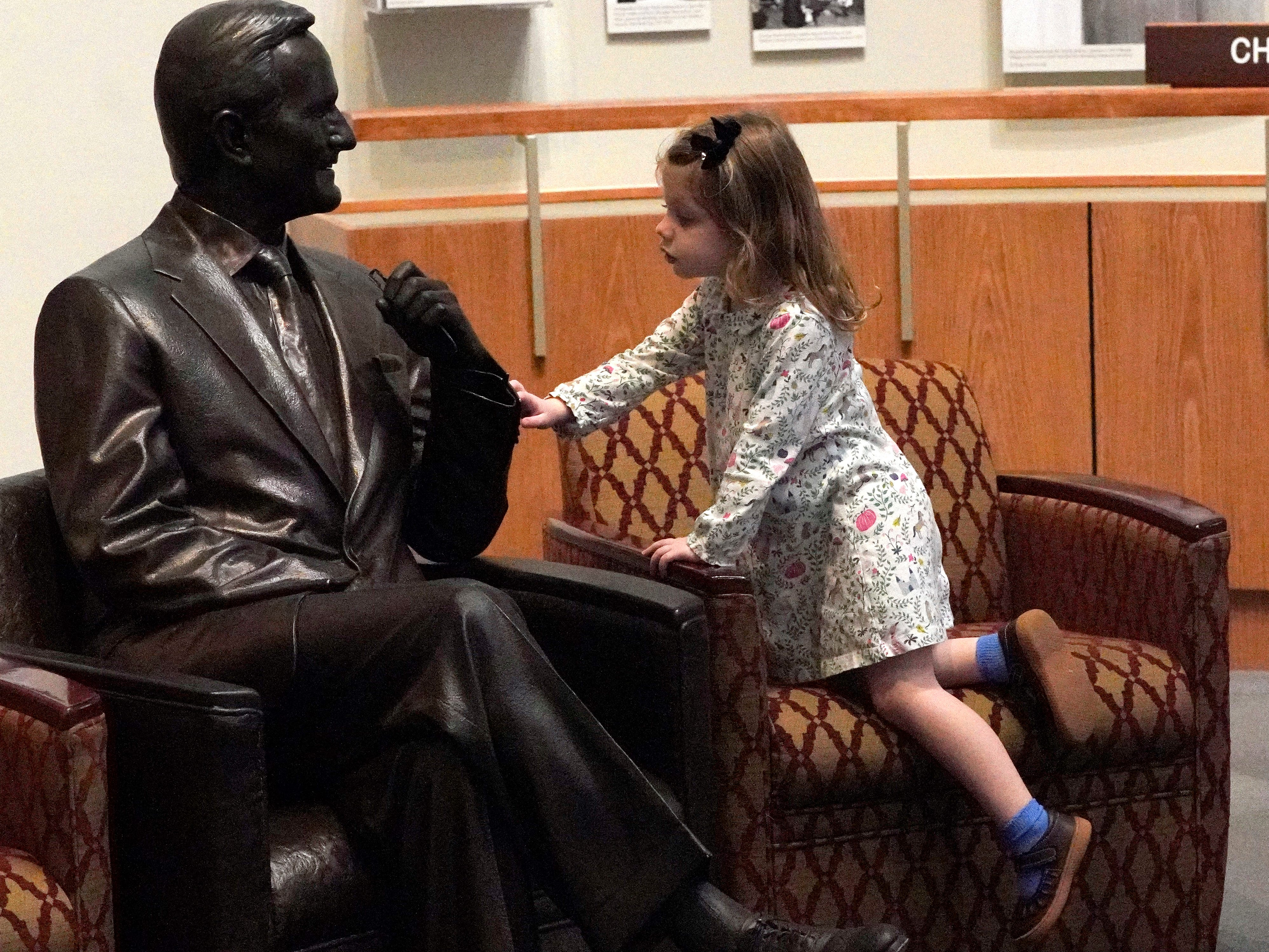 Caroline Western, 3, of College Station, Texas, touches at a statue of George H.W. Bush inside the George H.W. Bush Presidential Library and Museum Saturday, Dec. 1, 2018, in College Station.