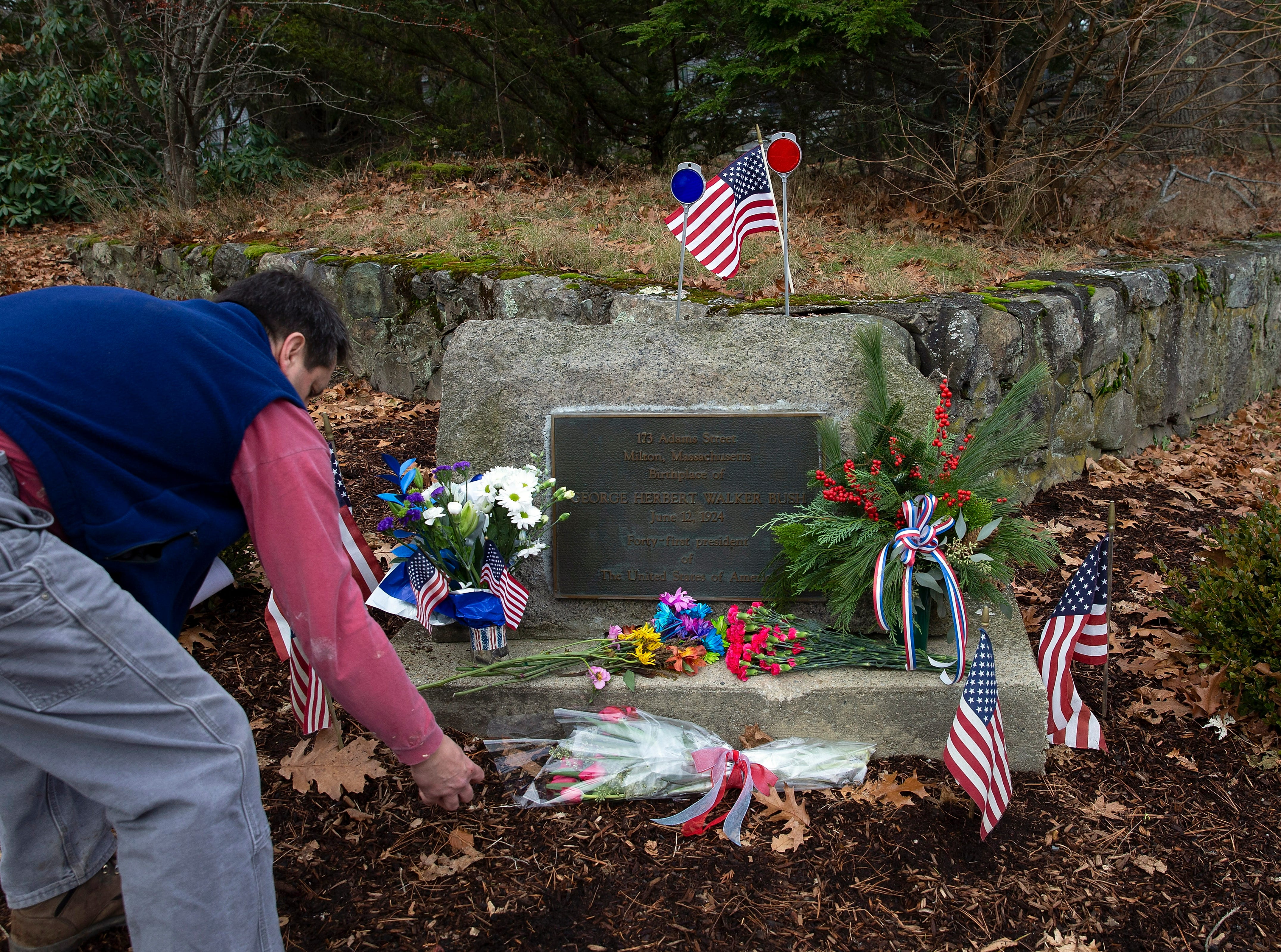A passer-by cleans off the historical marker near the birth home of former United States President George H. W Bush in Milton, Mass. on Dec. 1, 2018.