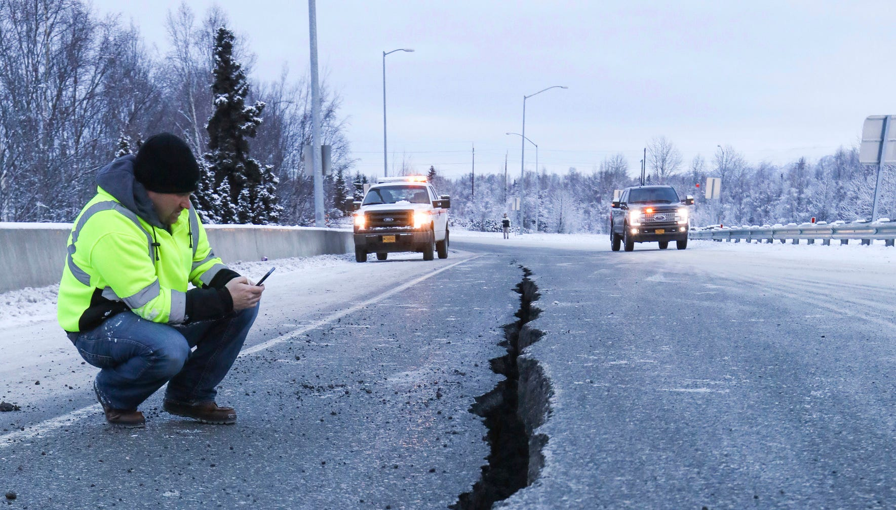 Marty Thurman with Granite construction inspects a crack in the road at the International Airport Road offramp on southbound Minnesota Blvd., in Anchorage, Alaska, Friday, Nov. 30, 2018. A state official says Ted Stevens Anchorage International Airport is open and operating at reduced capacity with delayed flights following back-to-back earthquakes.