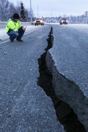 Marty Thurman of Granite Construction inspects a crack in the road Nov. 18, 2018, at the International Airport Road offramp in Anchorage, Alaska. The Anchorage area experienced a 7 magnitude earthquake that day.