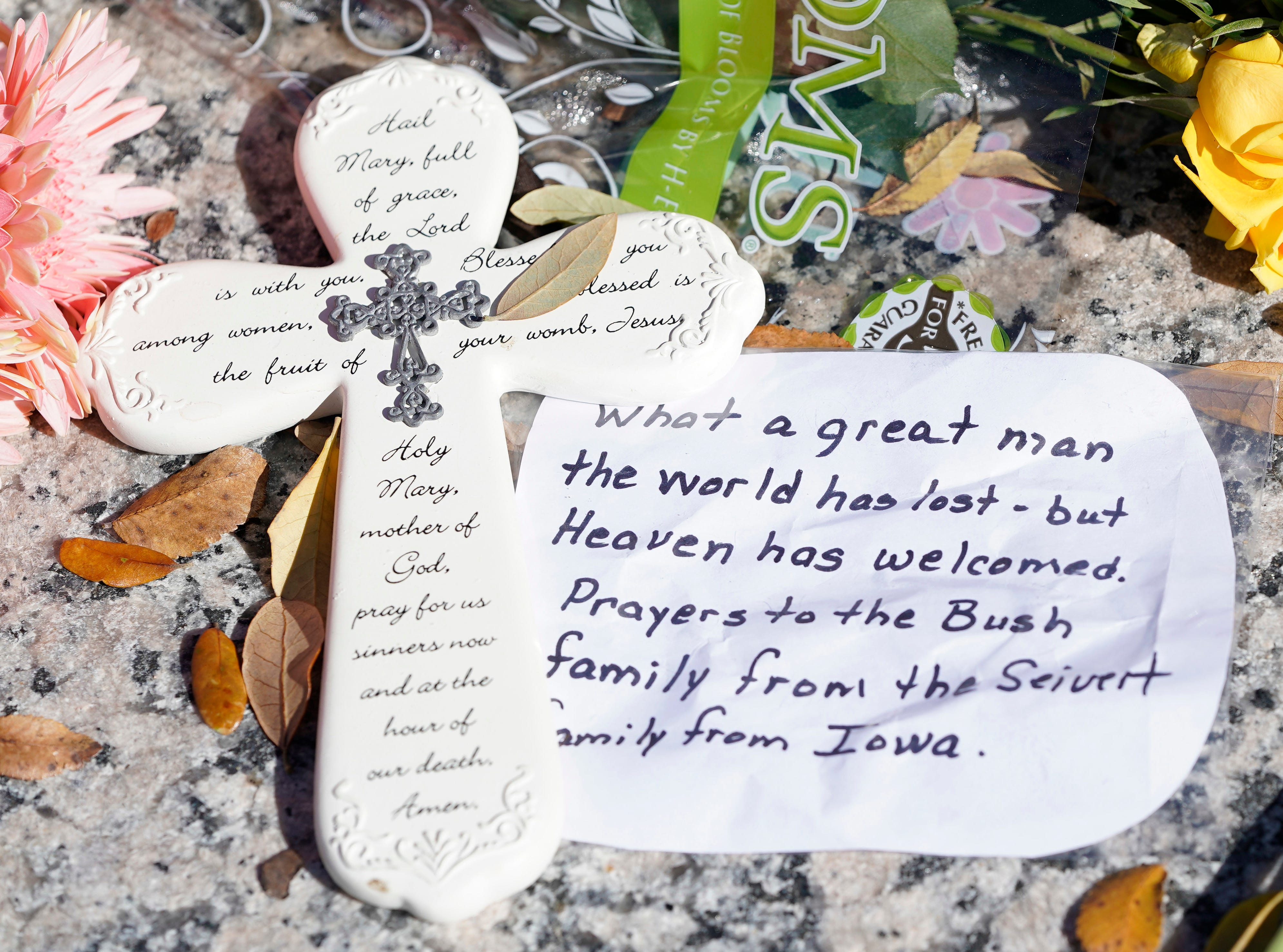 A messages lies among flowers left at the base of a statue of George H.W. Bush outside the George H.W. Bush Presidential Library and Museum Saturday, Dec. 1, 2018, in College Station.