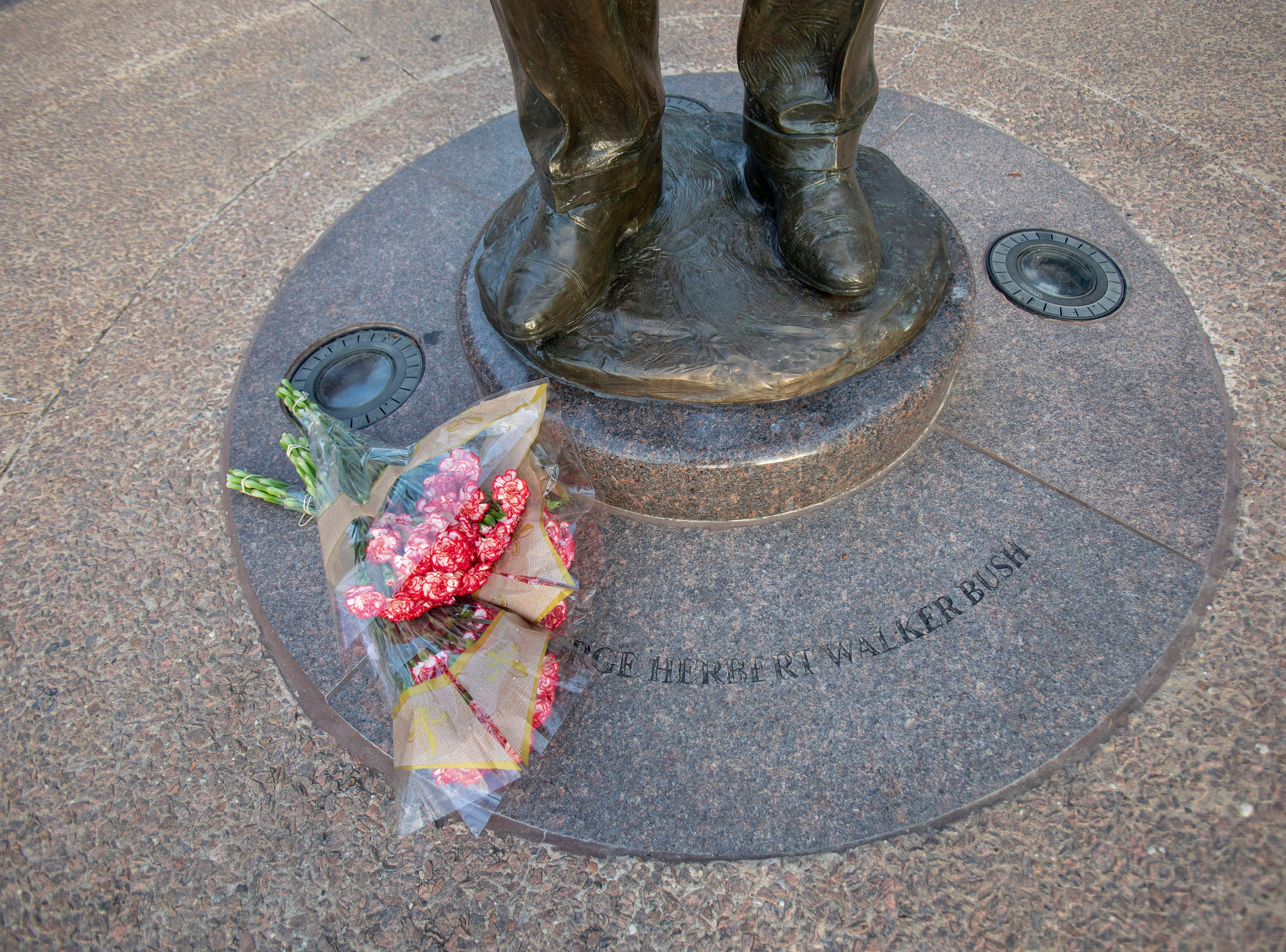 Flowers lay at the statue of former United States President George H.W. Bush near the Presidential Library in College Station, Texas on Dec. 1, 2018.