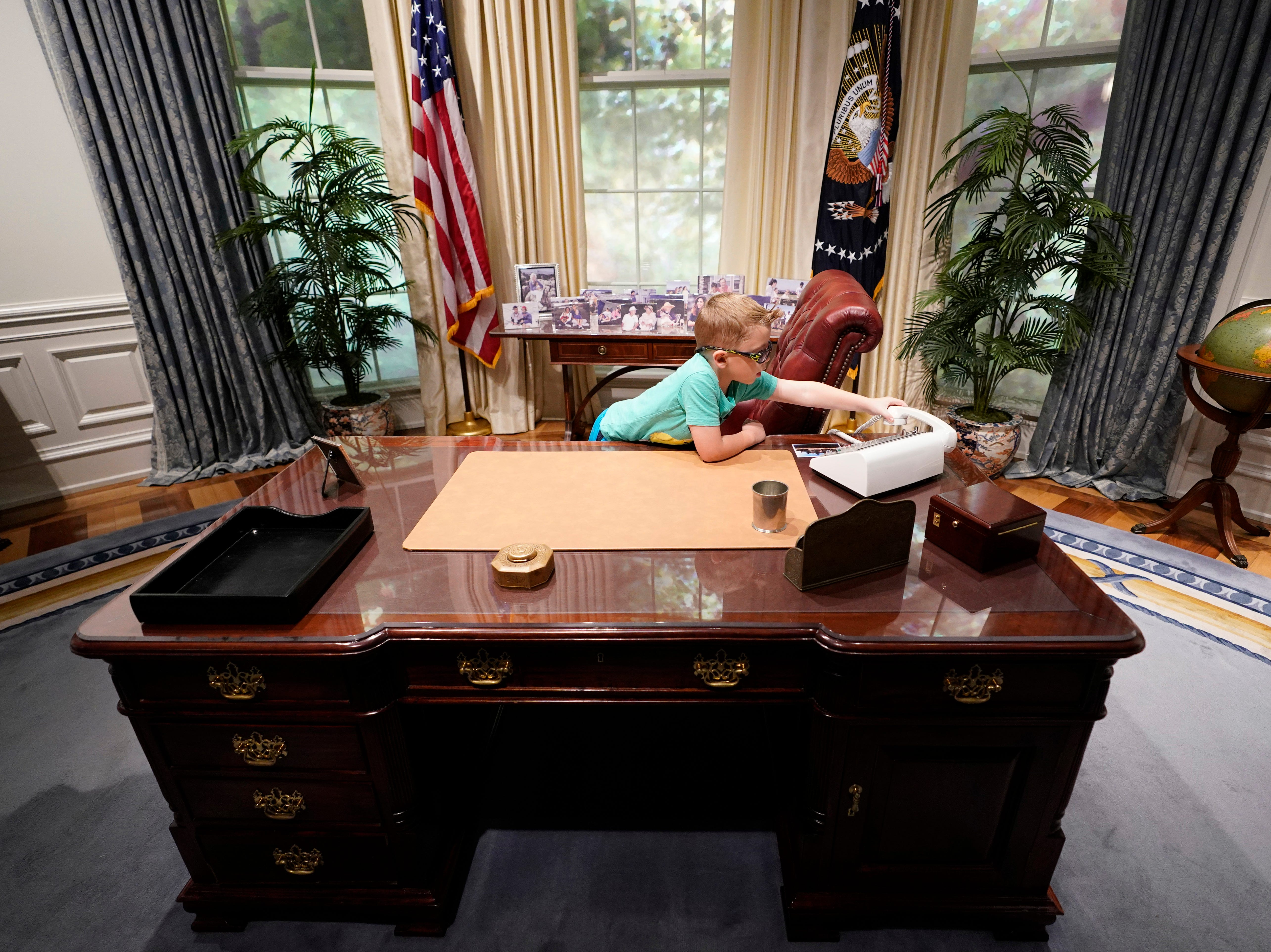 Kalob Duke, 6, of College Station, Texas, sits behind the desk in a replica of the Oval Office exhibit at the George H.W. Bush Library and Museum Saturday, Dec. 1, 2018, in College Station.