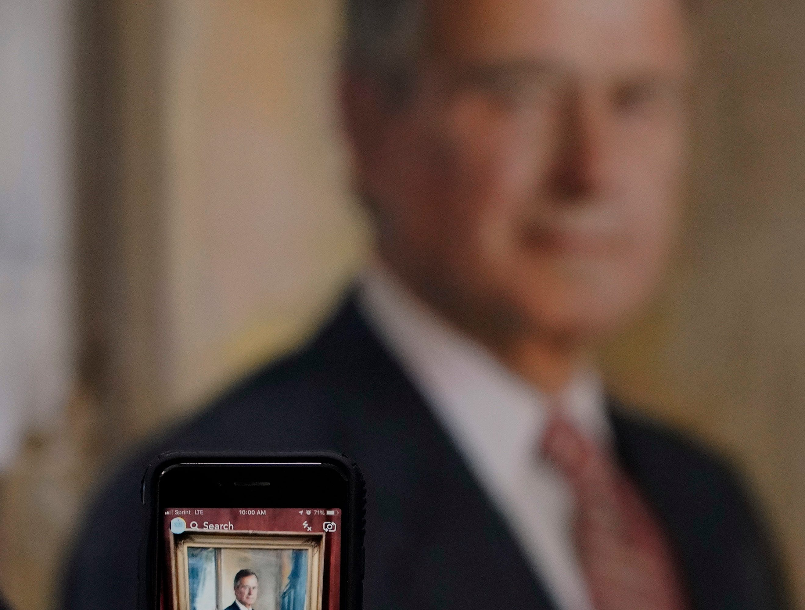 A visitor takes a photo of a painting of George H.W. Bush inside the George H.W. Bush Library and Museum Saturday, Dec. 1, 2018, in College Station.