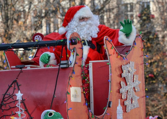 Santa Claus waves to people watching the City of Anderson Christmas Parade through downtown Sunday, December 2, 2018.