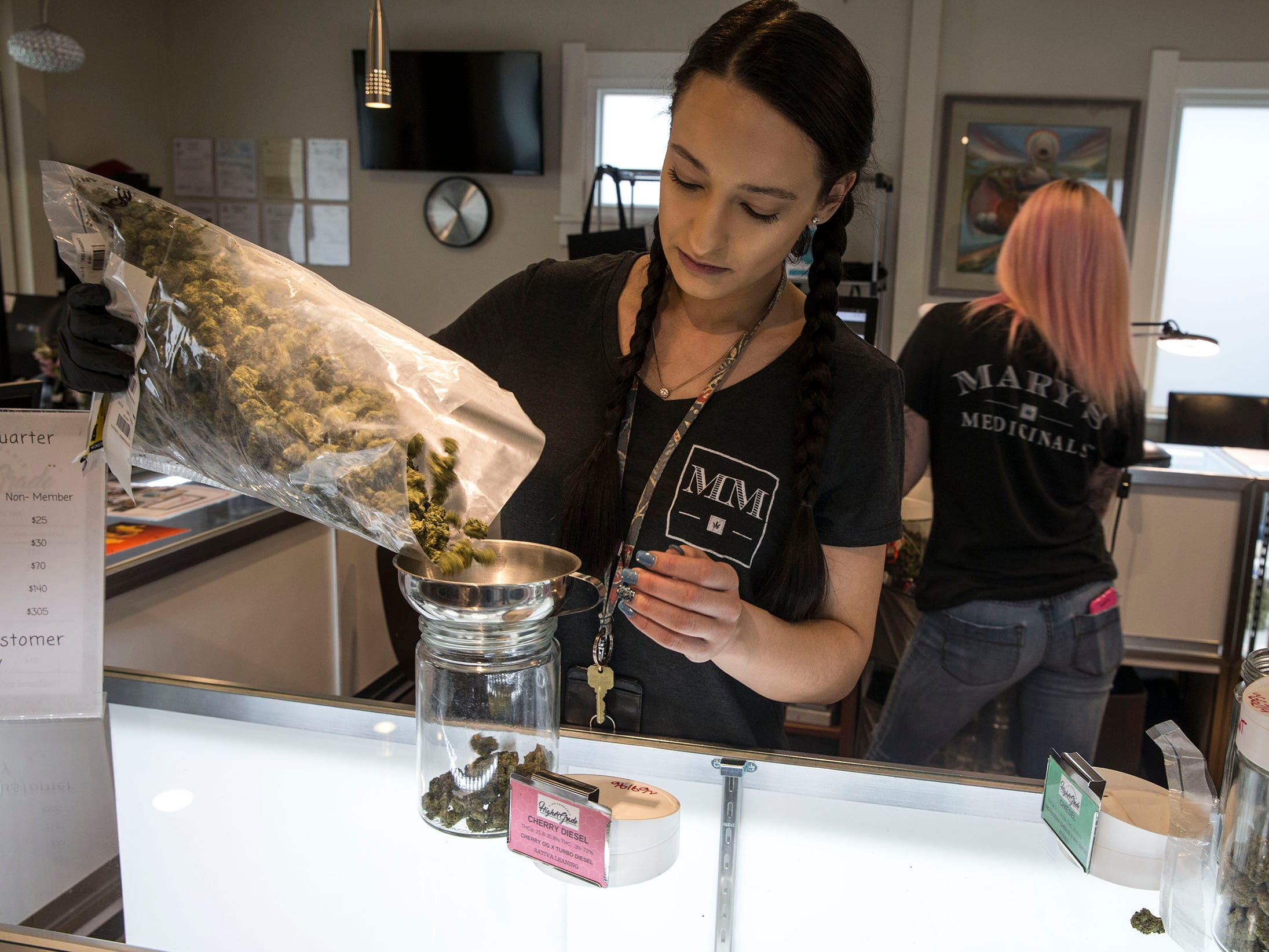 Raven Guillmette, store manager, measures out a strain of marijuana called Cherry Diesel. Higher Grade dispensary offers fine cannabis for medicinal purposes.  Denver, CO on Friday, April 13, 2018