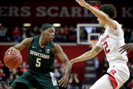 Michigan State guard Cassius Winston, left, drives against Rutgers guard Caleb McConnell