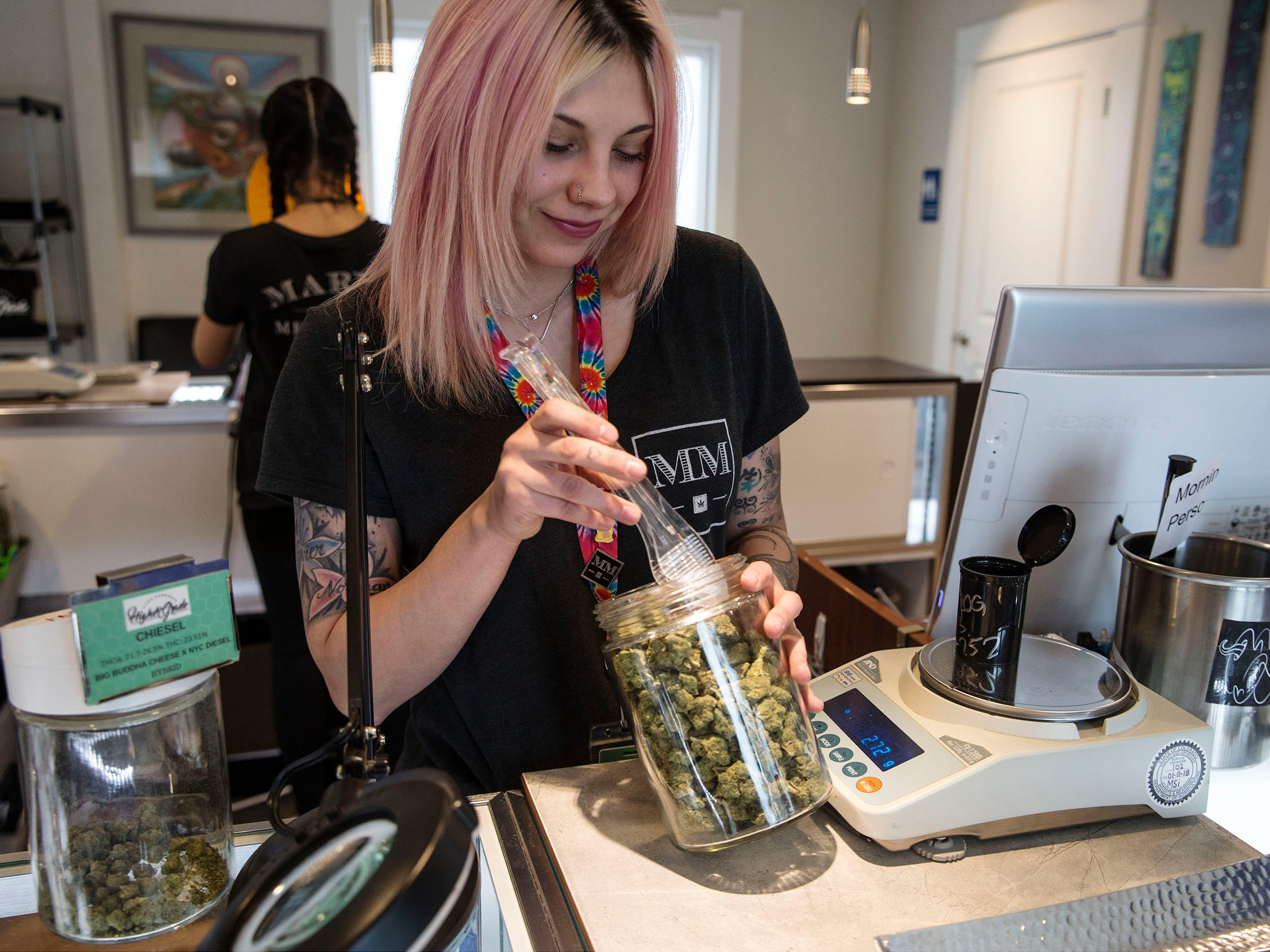Bud tender Summer Barker measures out marijuana flower for a medical customer. Higher Grade dispensary offers fine cannabis for medicinal purposes.   Denver, CO on Friday, April 13, 2018