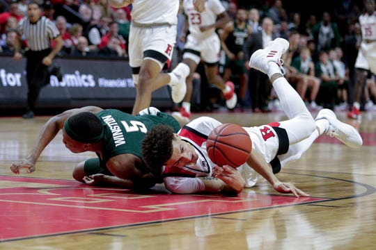 Michigan State Spartans guard Cassius Winston (5) battles for the ball against Rutgers Scarlet Knights guard Caleb McConnell (22)