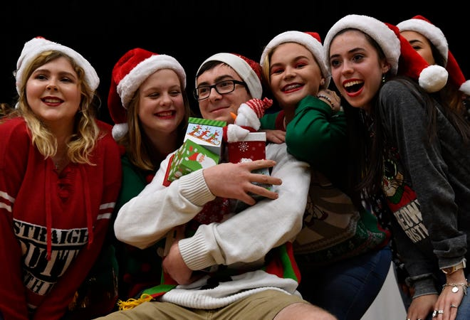 """Junior Alex Withers is surrounded by members of VocalPoint, the show choir at Wylie High School, during its performance of """"Santa Baby"""" at the Bulldog Christmas Market Thursday. This was the second year for the market which featured student-made products for sale in the high school's cafeteria."""