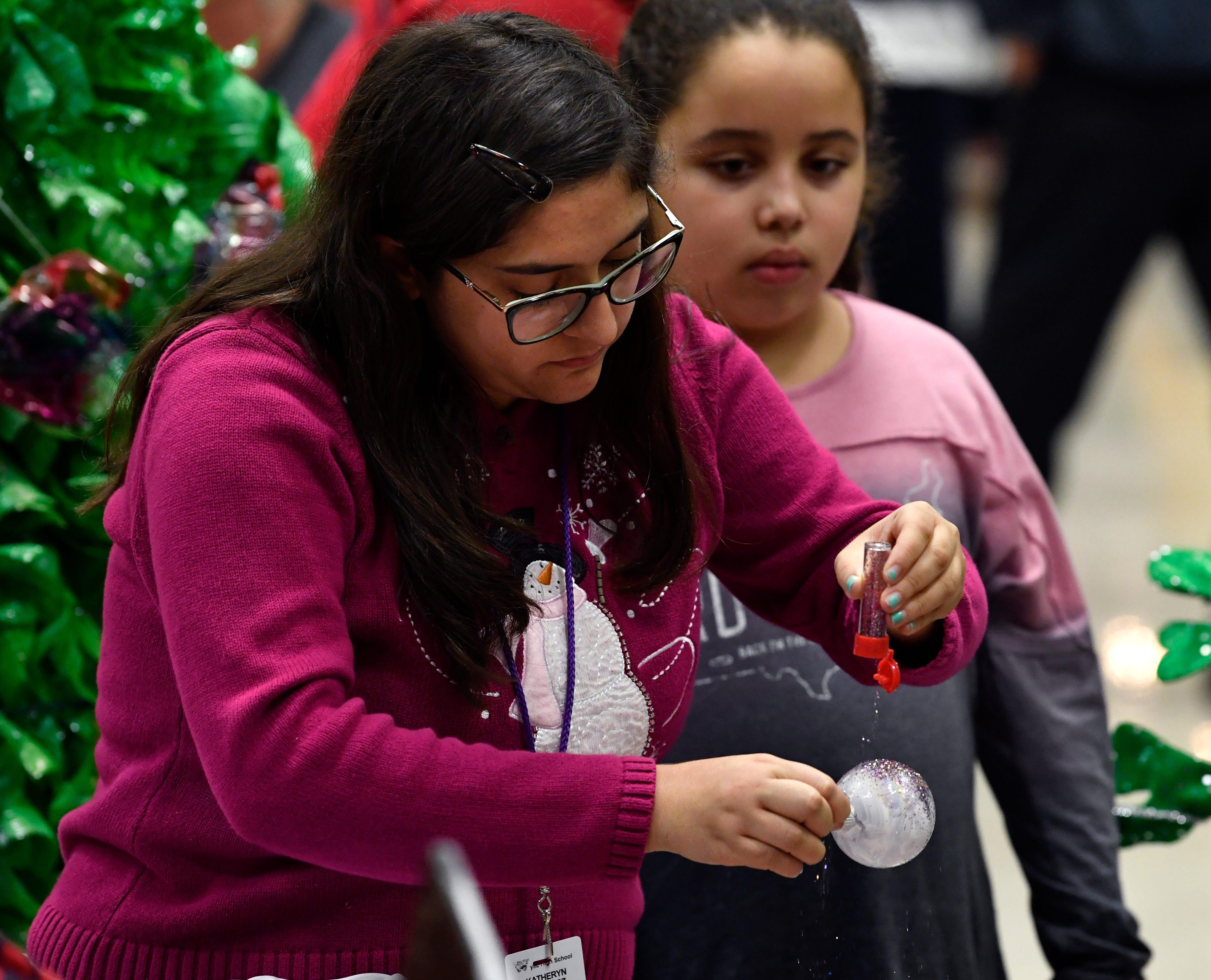 Katheryn Sanchez, a senior at Wylie High School, sprinkles glitter on an ornament during the Bulldog Christmas Market Thursday.