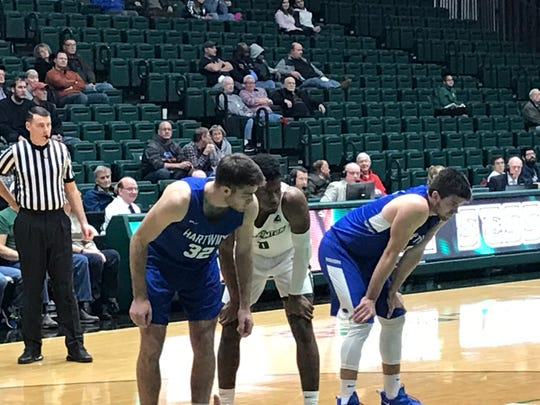 Hartwick College's Austin Haskell (32) and Patrick Garey flank Binghamton University's Richard Caldwell, Jr., during Saturday's exhibition at the Events Center.