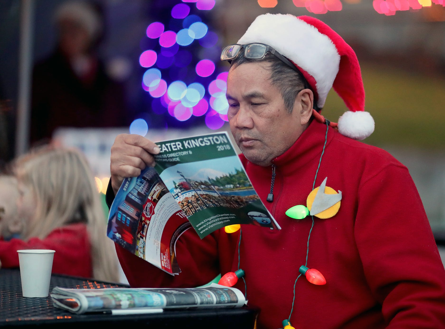 The Kingston Cove Christmas celebration on Saturday, December 1, 2018, at Mike Wallace Park in Kingston.The highlight of the event was the arrival of Santa and the Christmas tree, and park lighting.Jim Kaanana of Seattle reads up on Kingston as he waits for the tree lighting.