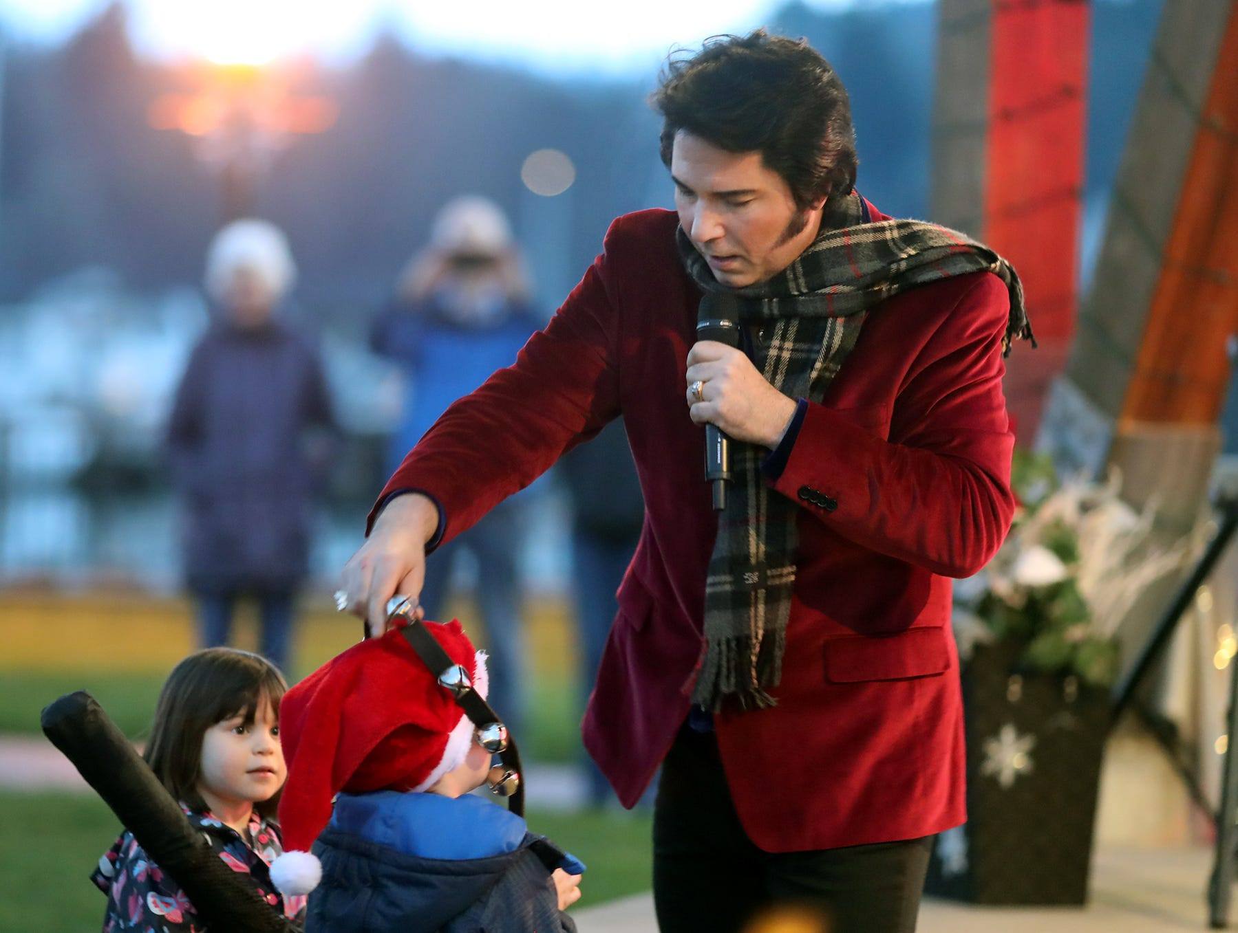 The Kingston Cove Christmas celebration on Saturday, December 1, 2018, at Mike Wallace Park in Kingston.The highlight of the event was the arrival of Santa and the Christmas tree, and park lighting. Elvis impersonator Danny Vernon puts bells on a youngster.