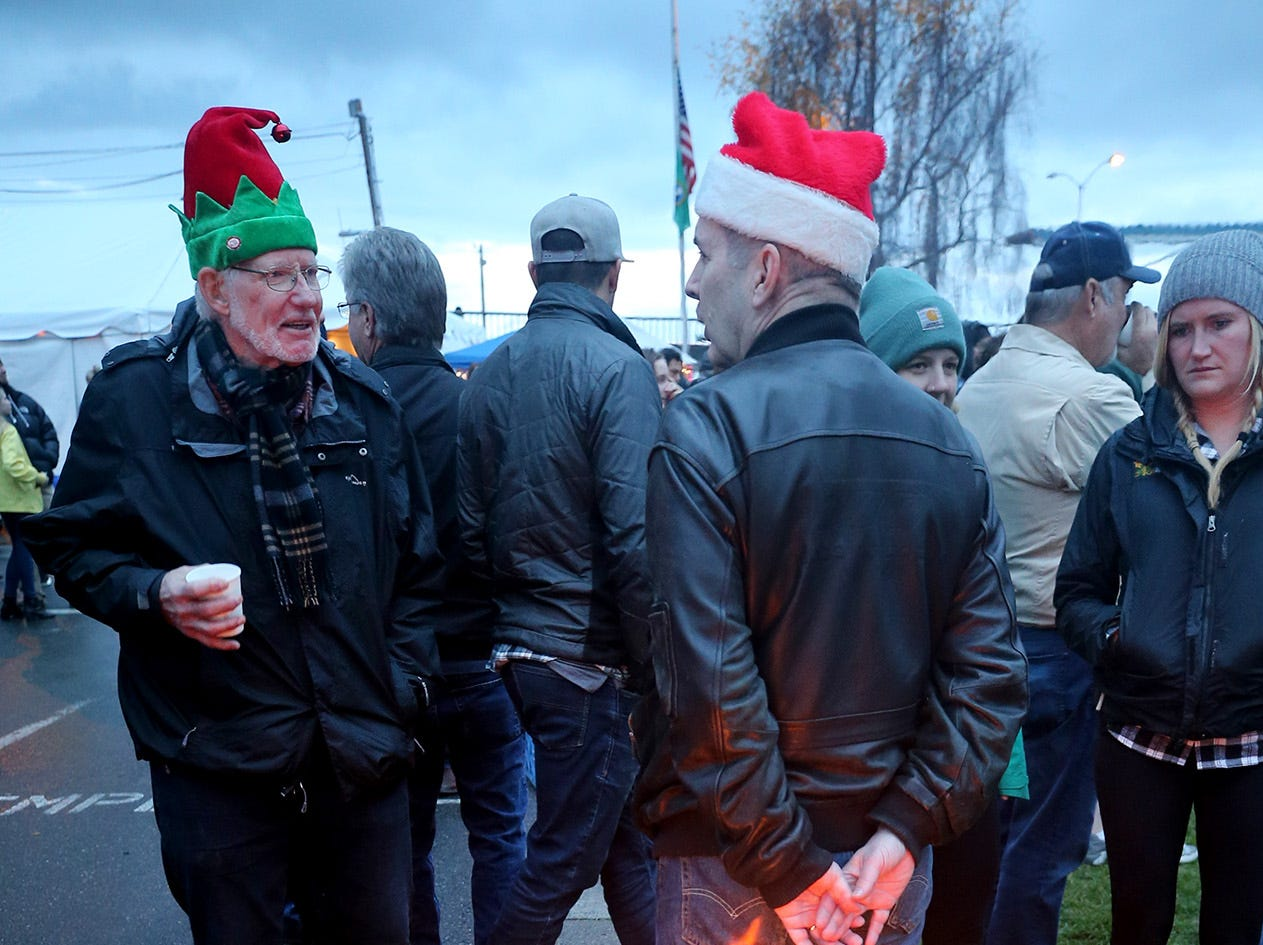 The Kingston Cove Christmas celebration on Saturday, December 1, 2018, at Mike Wallace Park in Kingston.The highlight of the event was the arrival of Santa and the Christmas tree, and park lighting. William Westwater, center, warms his hands by the bonfire as he talks with Rick Eveleth both from Kingston.
