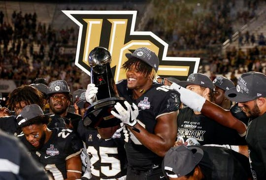 UCF Knights defensive lineman Titus Davis (10). Holds up the champions trophy following a win over Memphis Tigers at Spectrum Stadium.