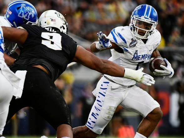 Trysten Hill #9 of the UCF Knights takes down Tony Pollard #1 of the Memphis Tigers for a loss of two yards during the first quarter of the American Athletic Championship at Spectrum Stadium on December 01, 2018 in Orlando, Florida. (Photo by Julio Aguilar/Getty Images)