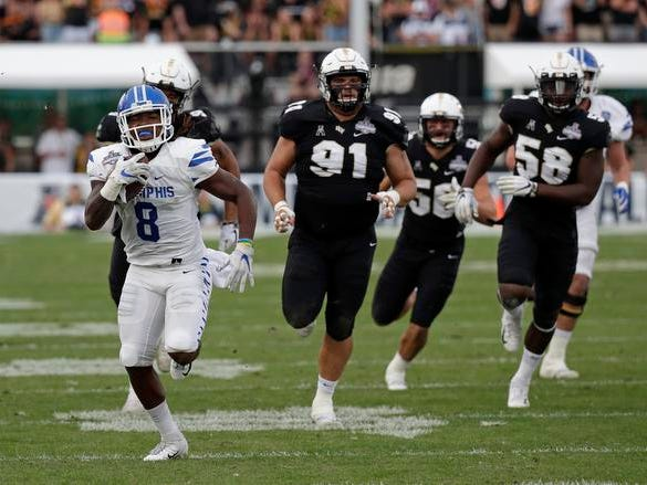 Memphis running back Darrell Henderson (8) runs for yardage against the Central Florida defense including defensive linemen Joey Connors (91) and Randy Charlton (58) during the first half of the American Athletic Conference championship NCAA college football game, Saturday, Dec. 1, 2018, in Orlando, Fla. (AP Photo/John Raoux)