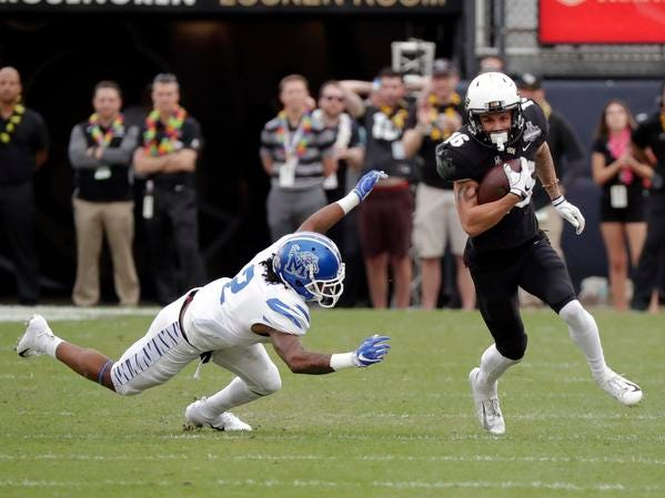Central Florida wide receiver Tre Nixon, right, runs past Memphis defensive back T.J. Carter after a reception during the first half of the American Athletic Conference championship NCAA college football game, Saturday, Dec. 1, 2018, in Orlando, Fla. (AP Photo/John Raoux)