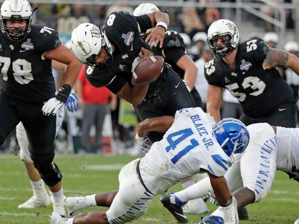 Central Florida quarterback Darriel Mack Jr., center top, fumbles the ball in the end zone as he is hit by Memphis defensive back Sanchez Blake Jr. (41) during the first half of the American Athletic Conference championship NCAA college football game, Saturday, Dec. 1, 2018, in Orlando, Fla. UCF recovered the fumble for a touchdown. (AP Photo/John Raoux)