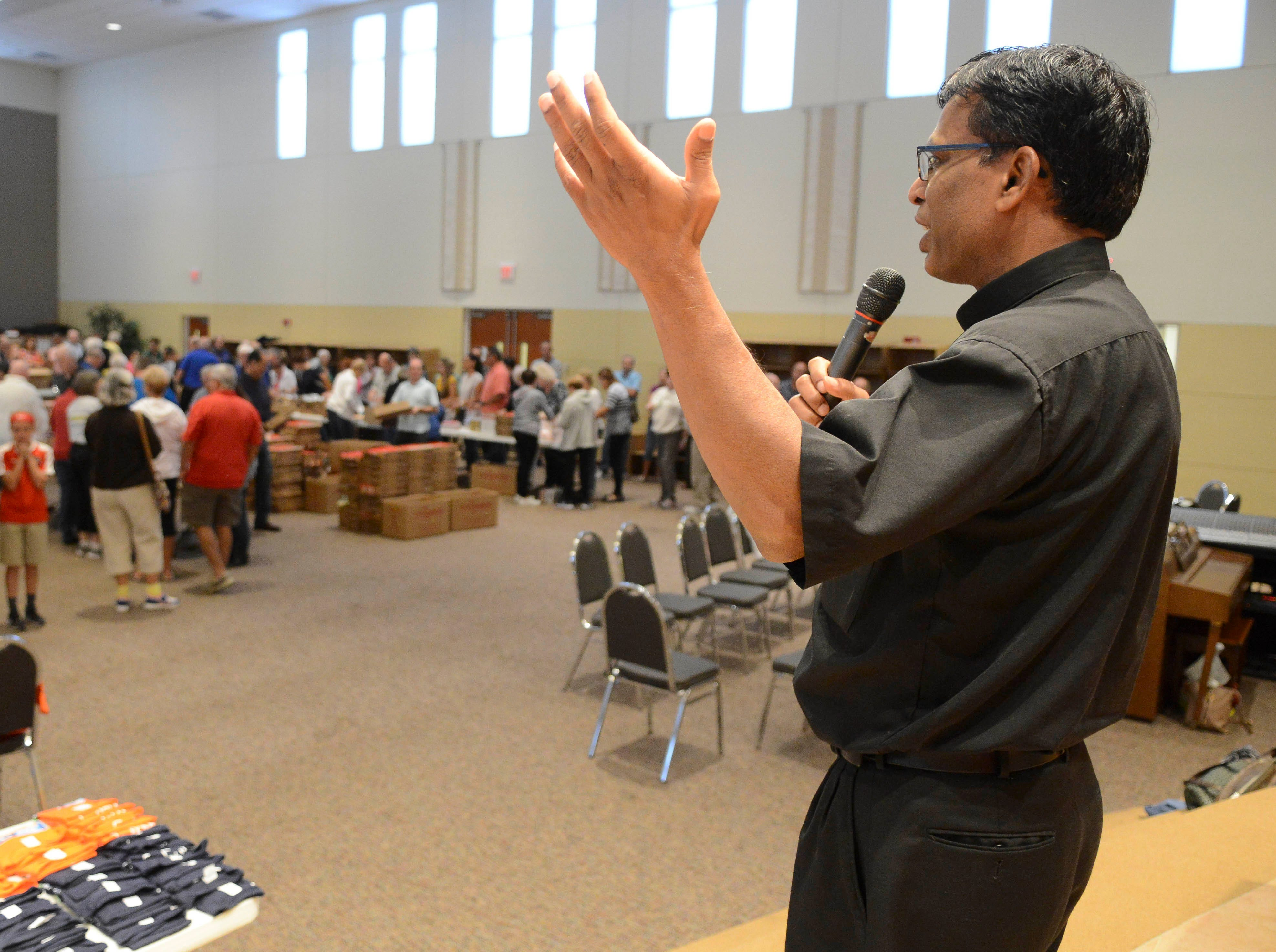 Father John Britto Antony of St. john the Evangelist church in VIera talks to the hundreds of volunteers gathered to help pack lunch kits for The Children's Hunger Project.