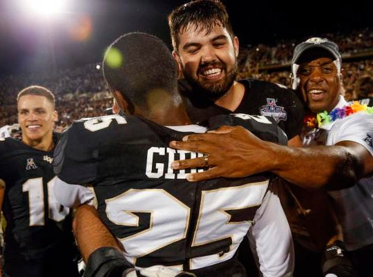 UCF Knights defensive back Kyle Gibson (25) and  offensive lineman Wyatt Miller (78) celebrate a win over Memphis Tigers at Spectrum Stadium.