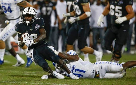 UCF Knights running back Adrian Killins Jr. (9) is brought down by Memphis Tigers defensive back Sanchez Blake Jr. (41) during the second half at Spectrum Stadium.