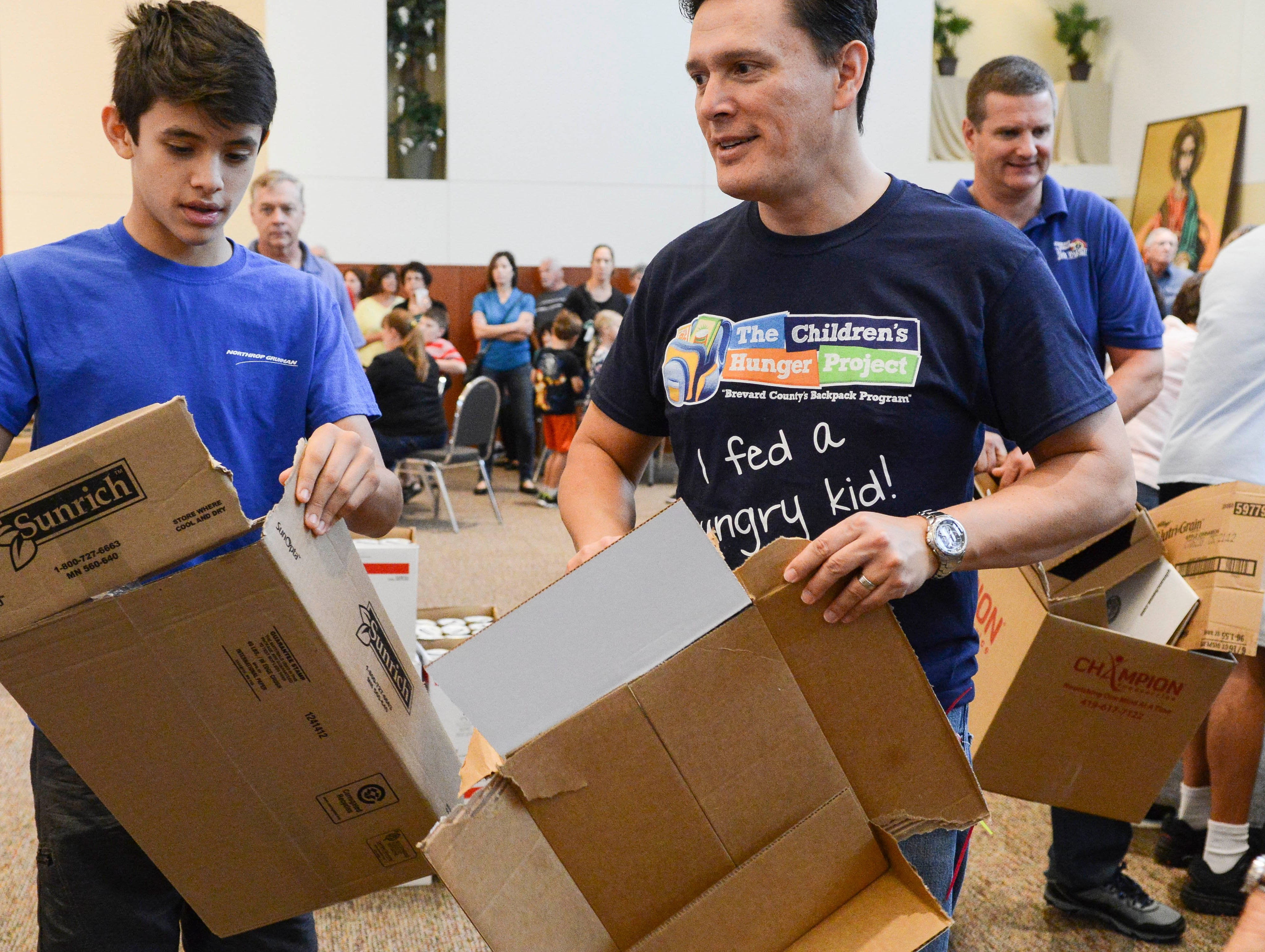 Matthew Tecson and his dad Art help break down empty boxes after using the contents to make food kits for children.  Hundreds of volunteers showed up at St. John the Evangelist Church in Viera to help pack lunch kits for The Children's Hunger Project.