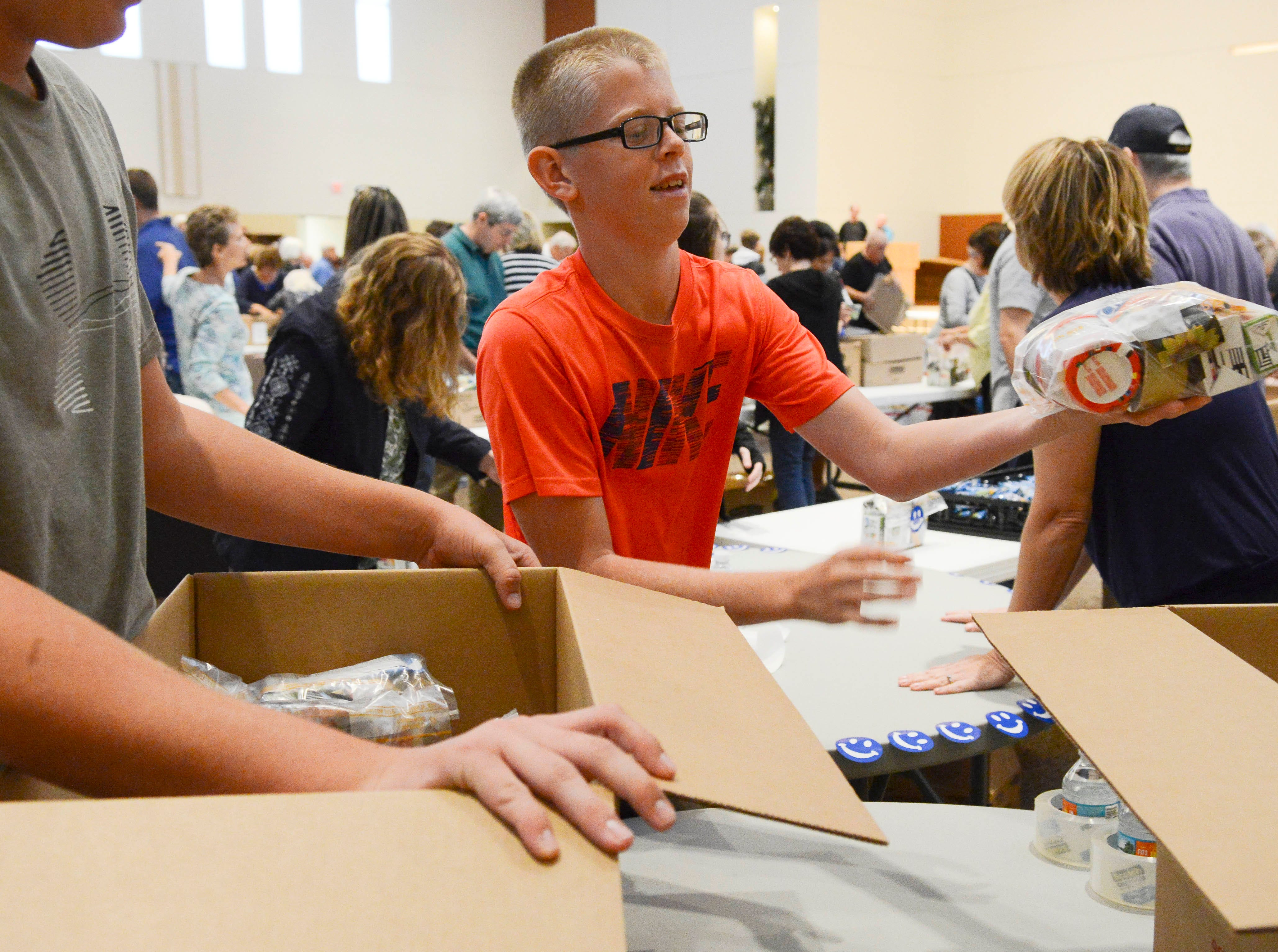 Colby Kessel helps load boxes with food packets Saturday morning  at St. John the Evangelist church in Viera. Hundreds of volunteers came to the church to help pack lunch kits for The Children's Hunger Project.