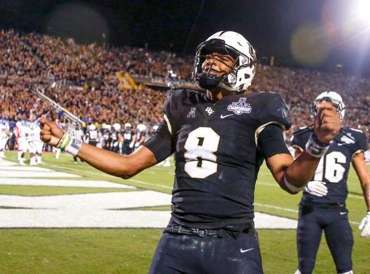 UCF Knights quarterback Darriel Mack Jr. (8) celebrates after a touchdown during the second half against the Memphis Tigers at Spectrum Stadium.