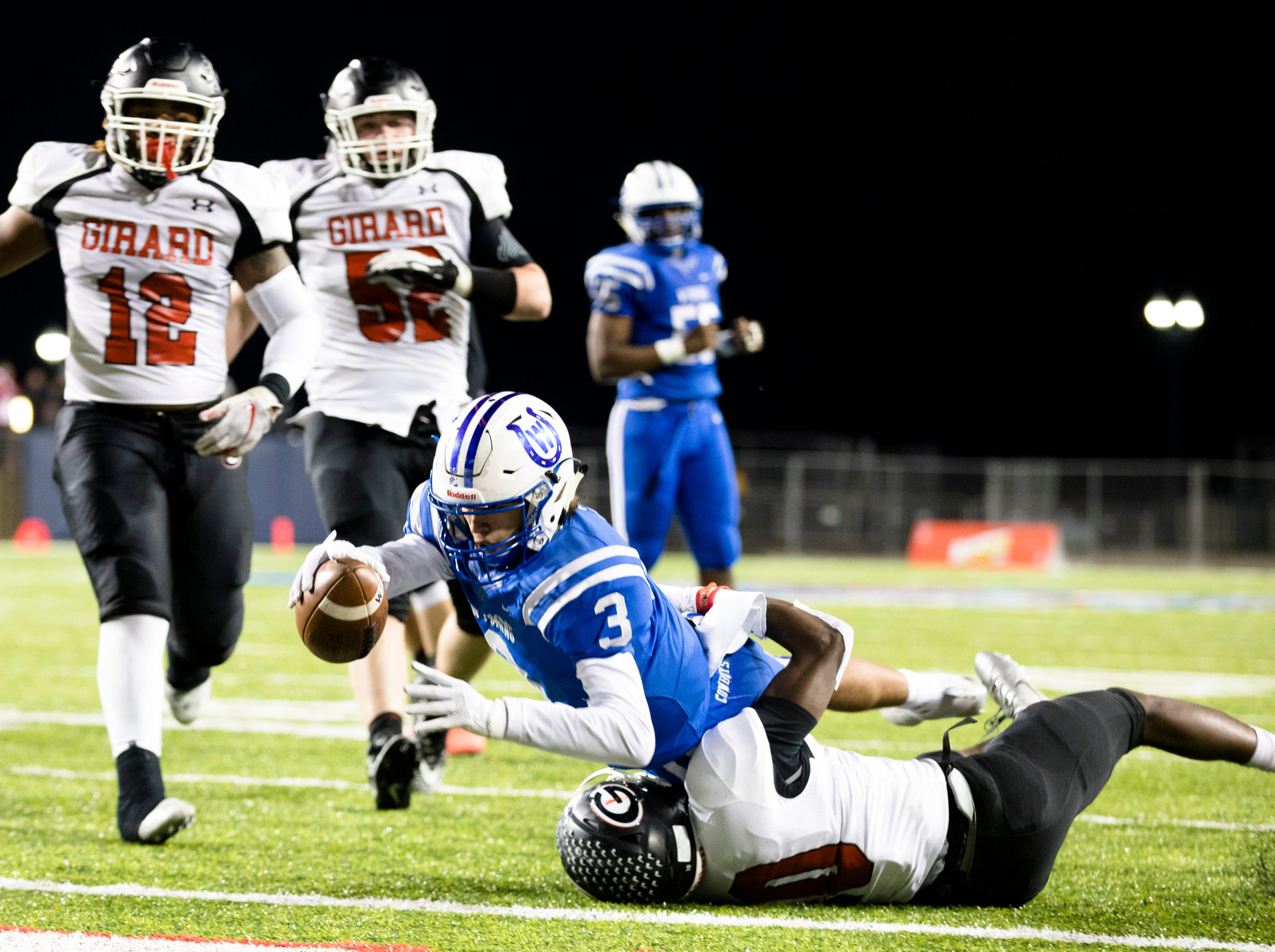 Wyoming's Evan Prater (3) dives over Girard's Jamil Bannister (10) into the end zone for a touchdown during the first half of the OHSAA Division IV State Championship football game between Wyoming and Girard on Saturday, Dec. 1, 2018, at Tom Benson Stadium in Canton.