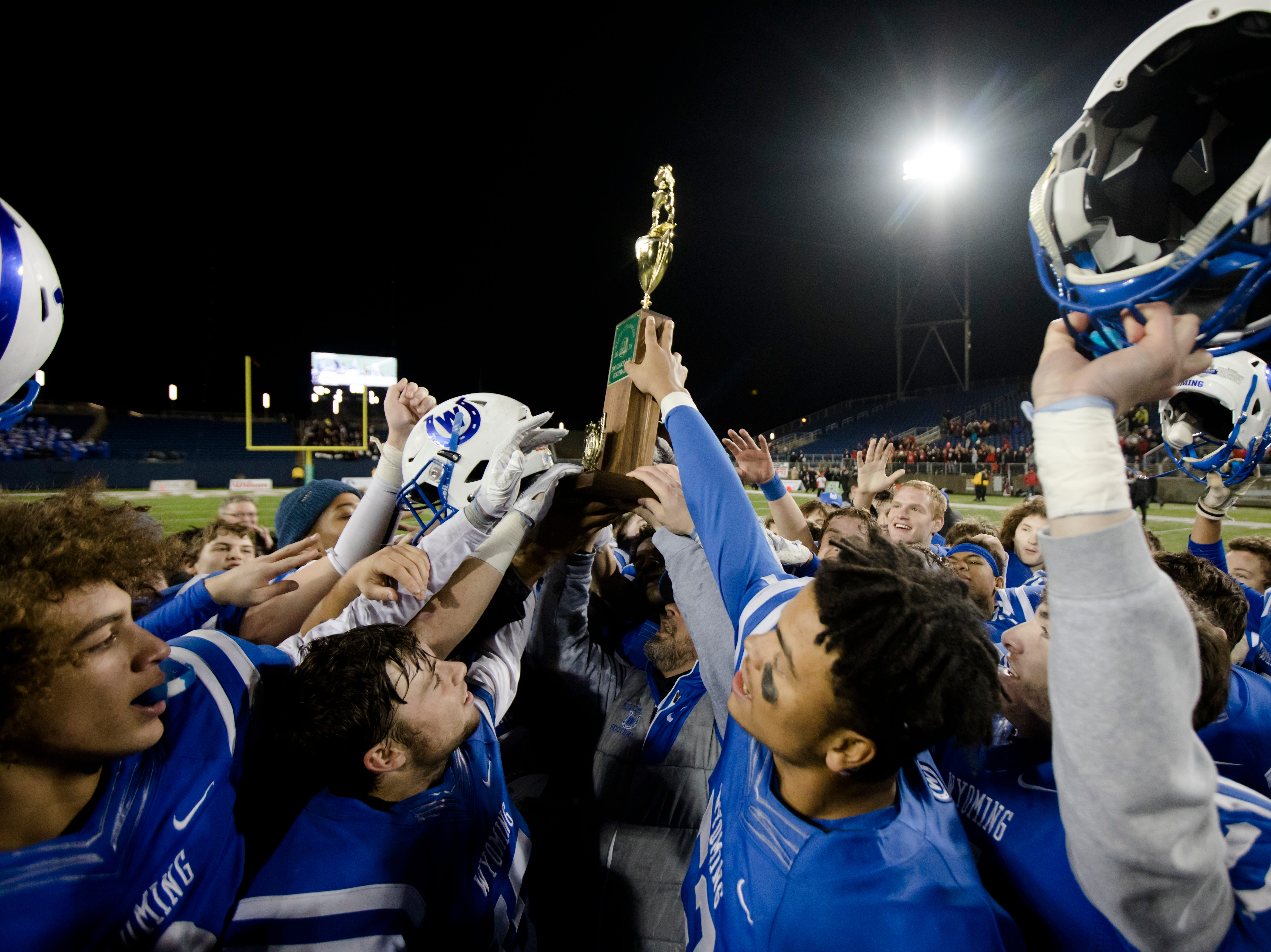 Wyoming head coach Aaron Hancock lifts the OHSAA Division IV State Championship football trophy on Saturday, Dec. 1, 2018, at Tom Benson Stadium in Canton. Wyoming defeated Girard 42-14.
