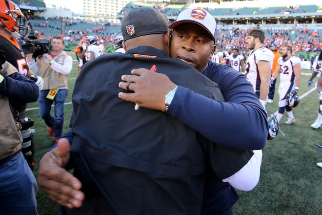 Denver Broncos head coach Vance Joseph and Cincinnati Bengals head coach Marvin Lewis embrace on the field after the Week 13 NFL football game, Sunday, Dec. 2, 2018, at Paul Brown Stadium in Cincinnati. The Denver Broncos won and the Cincinnati Bengals fell to 5-7 on the season with the loss.