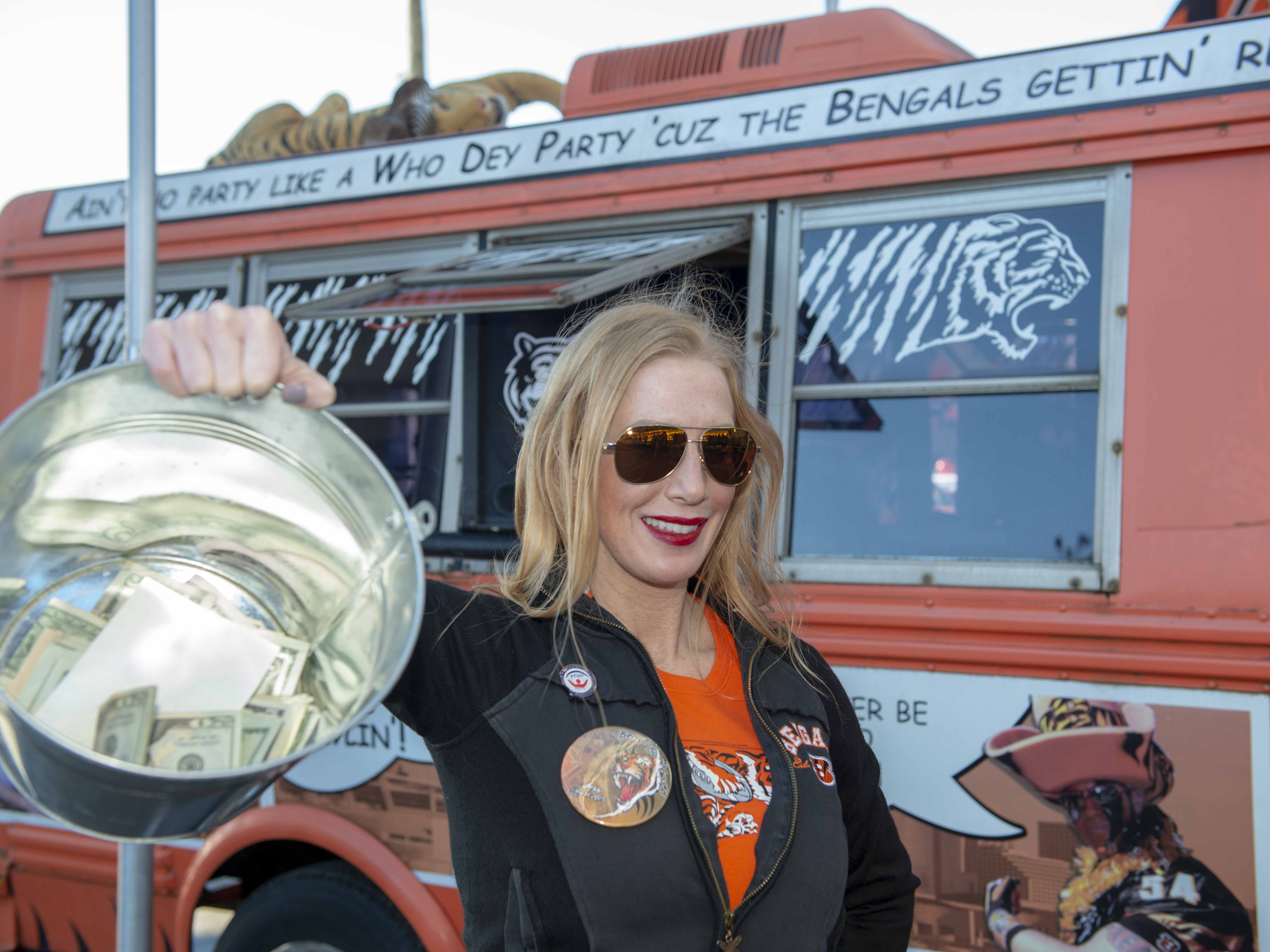 Cincinnati Bengals fans showed up for tailgating parties as the Cincinnati Bengals hosted the Denver Broncos at Paul Brown Stadium Sunday, December 2, 2018. Jess Conley holds up her bucket of money collected for the Maskvsmohawk.com charity.  The winner of the Bengals vs. Chargers game will donte the collected money to their favorite charity. If the Bengals win the money will go to the Alzheimers Foundation or if the Broncos win then the money will go to the Lupus Foundation.