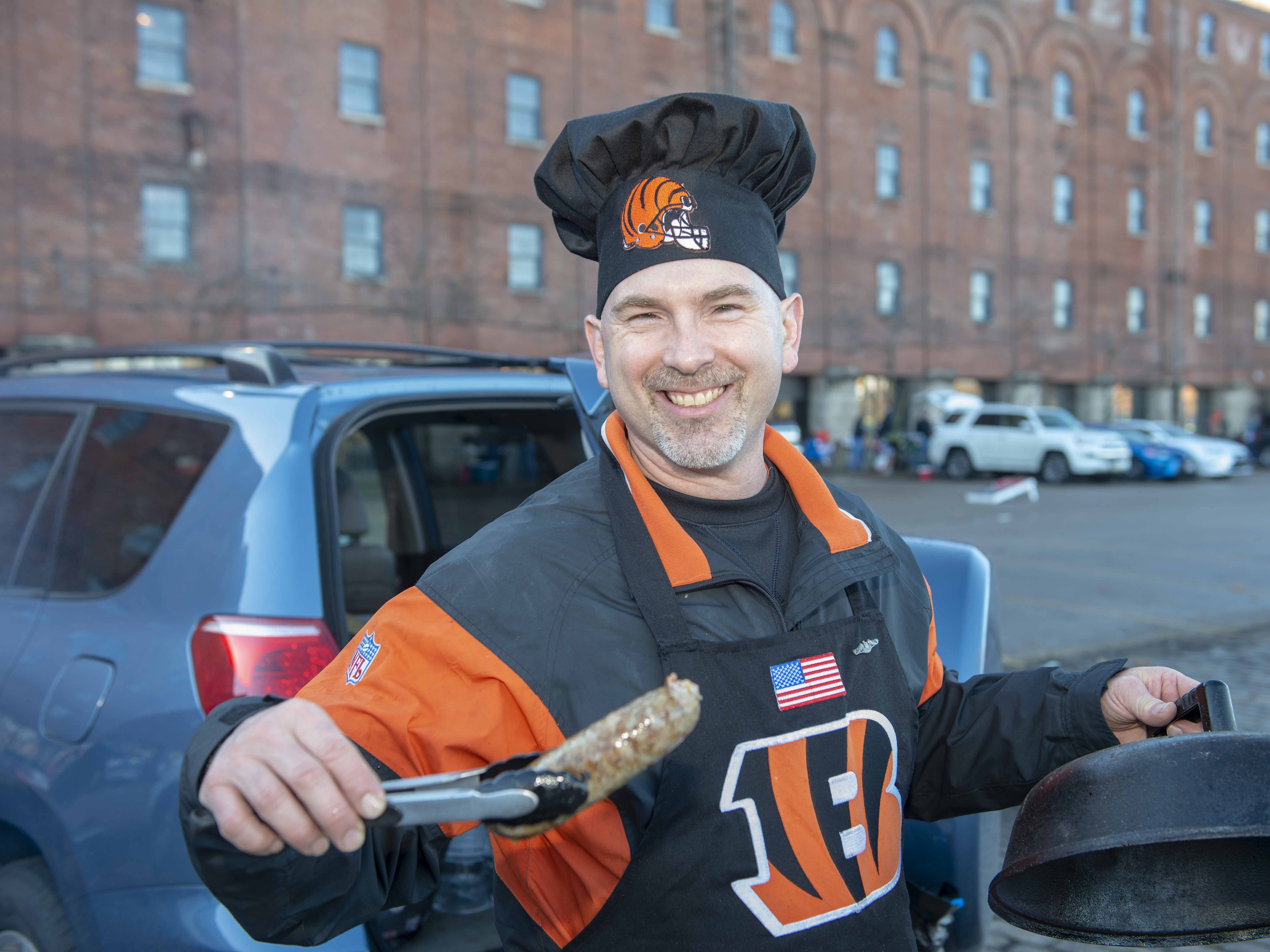 Cincinnati Bengals fans showed up for tailgating parties as the Cincinnati Bengals hosted the Denver Broncos at Paul Brown Stadium Sunday, December 2, 2018. Ken Adams of West Price Hill grills up some Italian sausages.