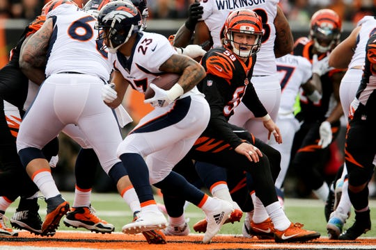 Cincinnati Bengals outside linebacker Nick Vigil (59) is unable to tackle Denver Broncos running back Devontae Booker (23) in the first quarter of a Week 13 NFL football game, Sunday, Dec. 2, 2018, at Paul Brown Stadium in Cincinnati.