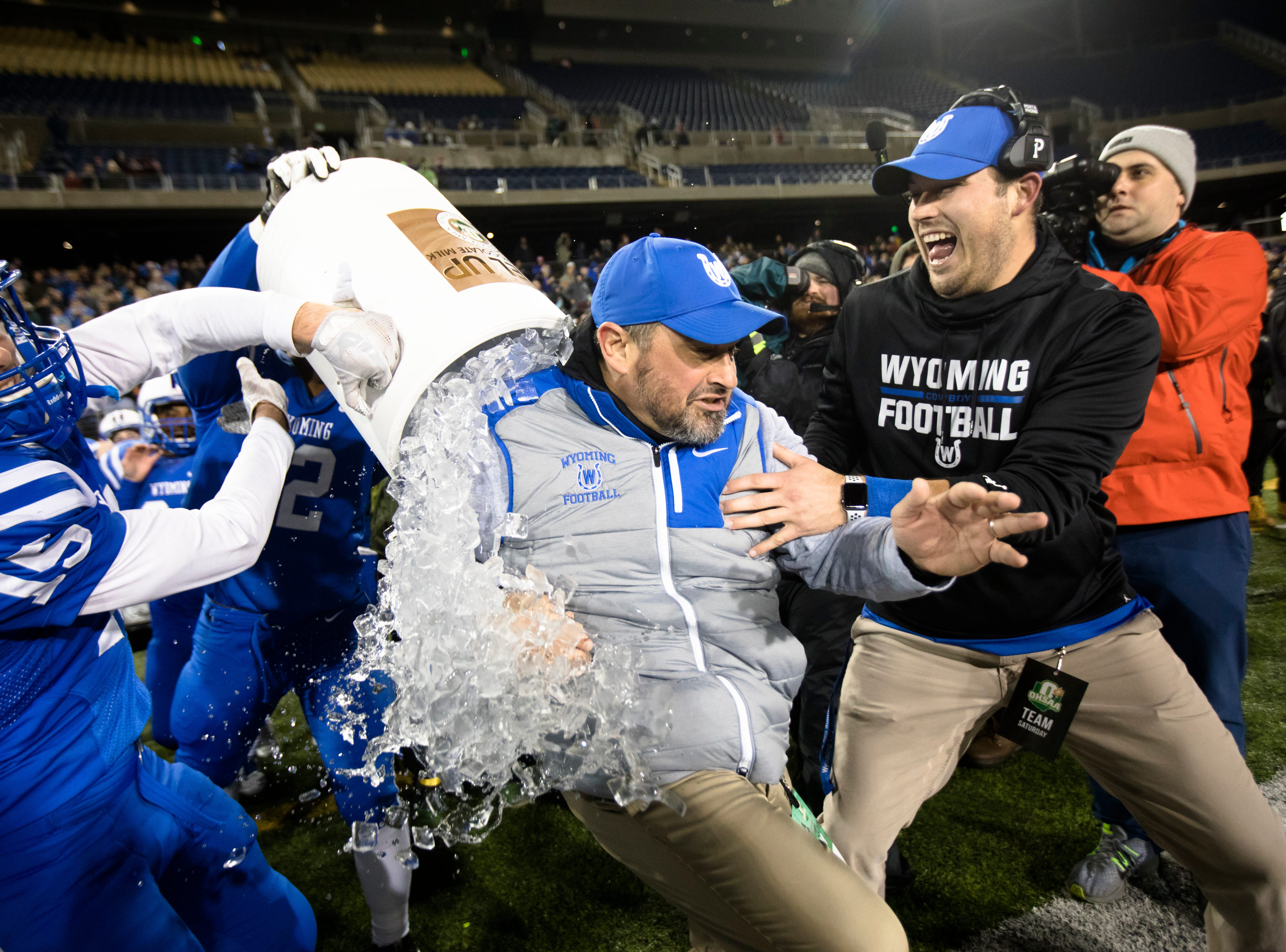 Wyoming's Perry McMichen (15) dunks Wyoming head coach Aaron Hancock as they win the OHSAA Division IV State Championship football game between Wyoming and Girard on Saturday, Dec. 1, 2018, at Tom Benson Stadium in Canton. Wyoming defeated Girard 42-14.