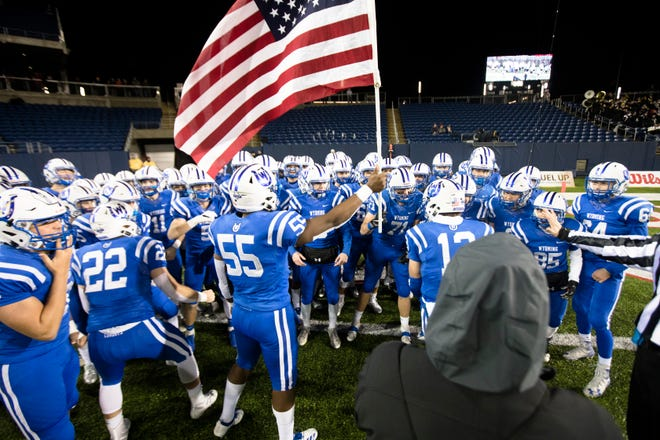 Wyoming's Hasan Black (55) holds the American flag before the first half of the OHSAA Division IV State Championship football game between Wyoming and Girard on Saturday, Dec. 1, 2018, at Tom Benson Stadium in Canton.