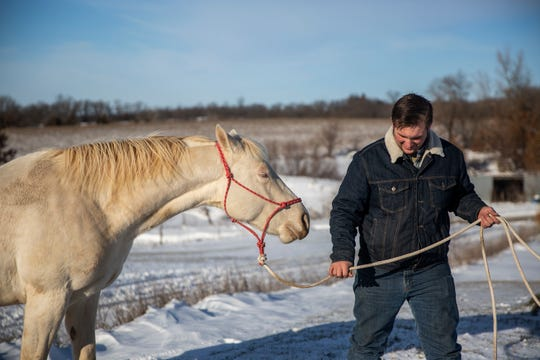 Cody Miller, 33, spends time with his horse Moon on his farm outside of Murray on Tuesday, Nov. 27, 2018, in southern Iowa. Miller, a veteran, says he can find peace while working with horses.