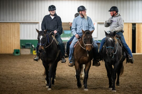 "Scott Reaney, a Navy veteran, Carroll ""Hippie"" Waser, a Marine veteran, and Lynn Winkelmann, equine activity director at Wildwood Hills Ranch of Iowa, ride horses in the Wildwood Hills arena on Thursday, Nov. 15, 2018, near St. Charles."
