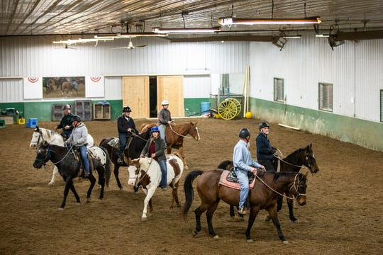 A group of military veterans, under the direction of Lynn Winkelmann, ride horses in the arena at Wildwood Hills Ranch of Iowa on Thursday, Nov. 15, 2018, near St. Charles.