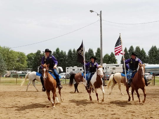 Military veterans who met at Wildwood Hills Ranch of Iowa carry the American Flag in parades and at fairs in central Iowa.