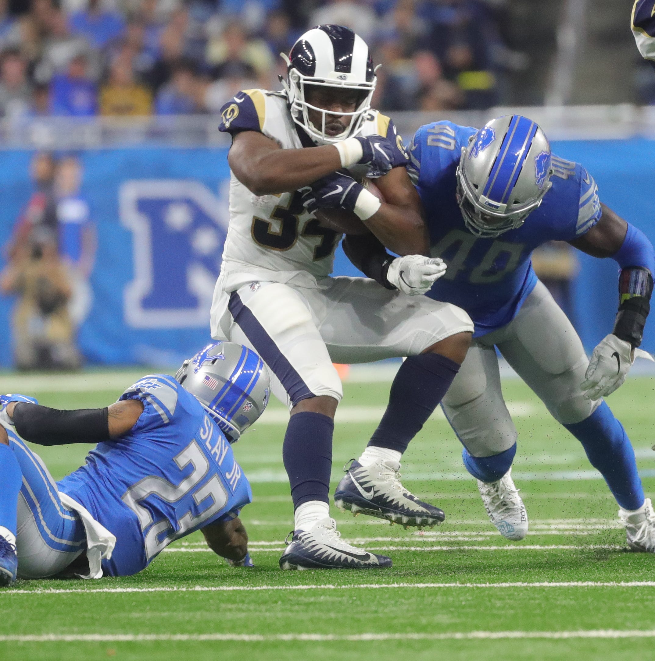 Lions cornerback Darius Slay, left, and linebacker Jarrad Davis tackle Rams running back Malcolm Brown during the first half on Sunday, Dec. 2, 2018, at Ford Field.