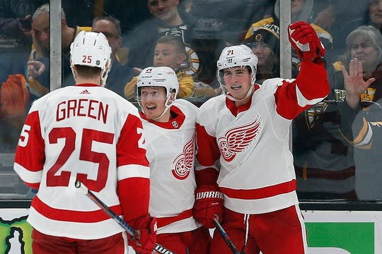 Dylan Larkin, right, celebrates his goal with teammates Gustav Nyquist, center, and Mike Green during the second period against the Bruins.