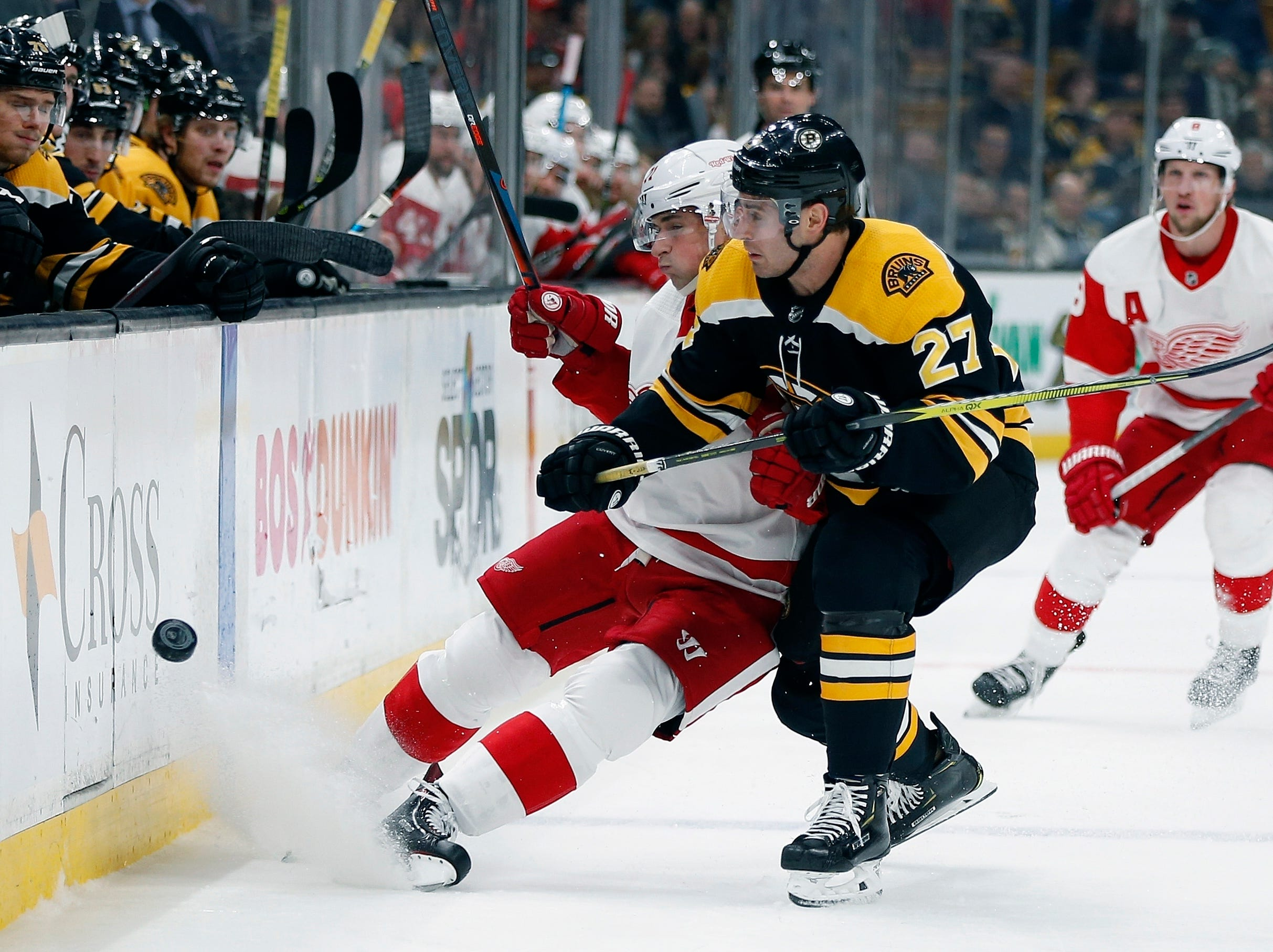 Boston Bruins' John Moore (27) battles Detroit Red Wings' Dylan Larkin, center left, for the puck during the first period in Boston, Saturday, Dec. 1, 2018.