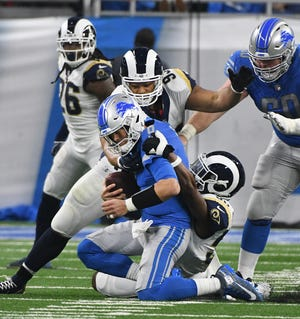 Lions quarterback Matthew Stafford is sacked by the Rams' Cory Littleton, with Rams defensive tackle Ndamukong Suh finishing it up, in the first quarter.