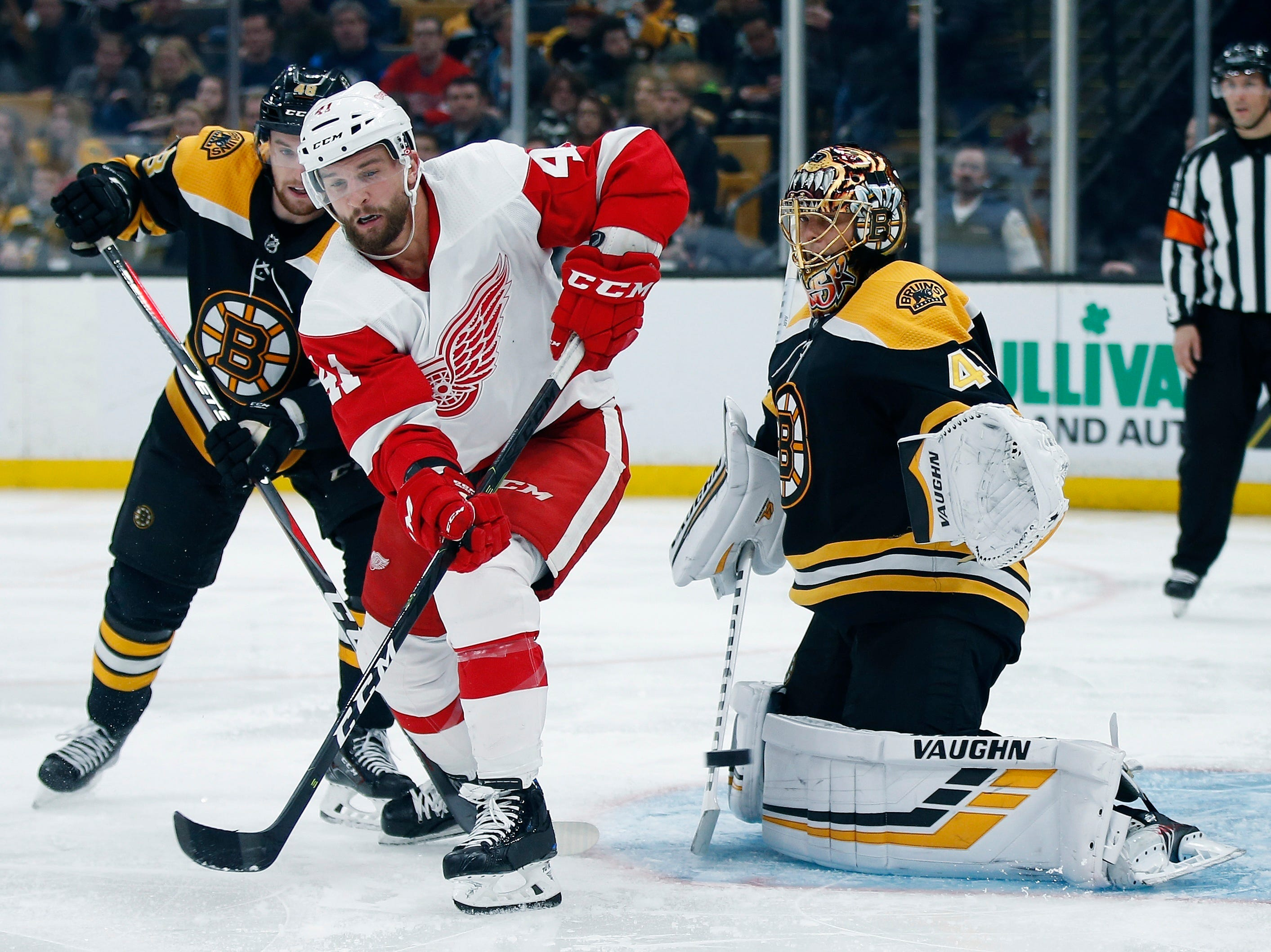 The puck goes wide of Boston Bruins' Tuukka Rask (40) as teammate Matt Grzelcyk (48) defends against Detroit Red Wings' Luke Glendening (41) during the third period.