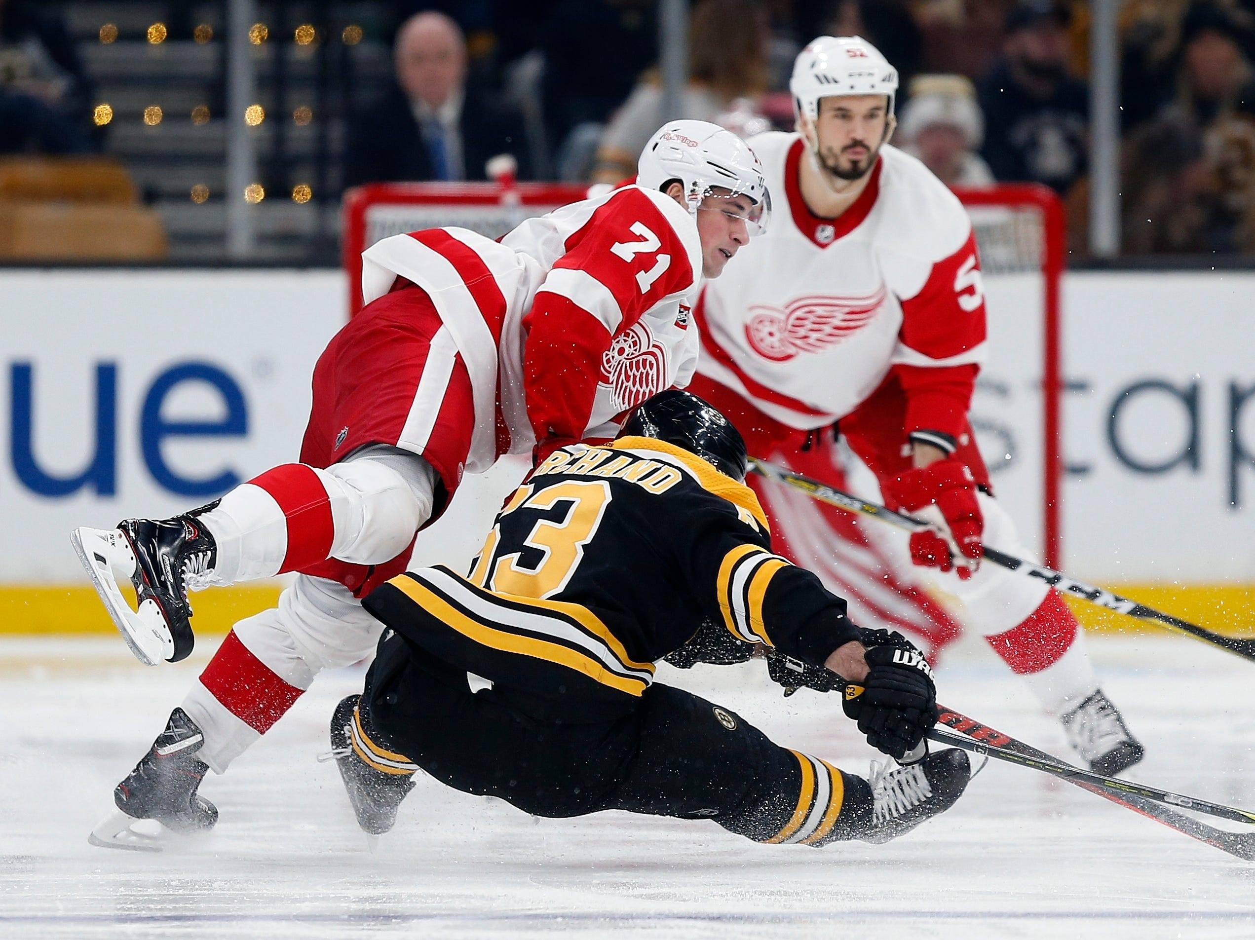 Detroit Red Wings' Dylan Larkin (71) and Boston Bruins' Brad Marchand (63) collide during the third period.